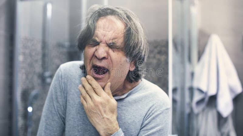 Mature man yawning in bathroom. Mature man yawning in  bathroom royalty free stock image