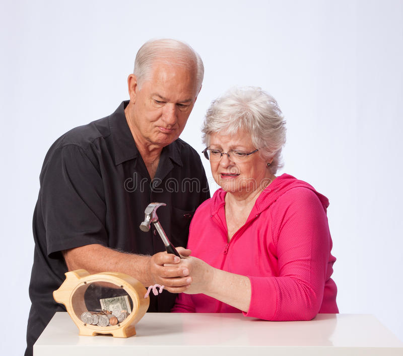 Mature Married Couple Breaking into Piggy Bank. Retirement aged married couple are about to break the piggy bank on white background. The husband and wife, ready royalty free stock photo