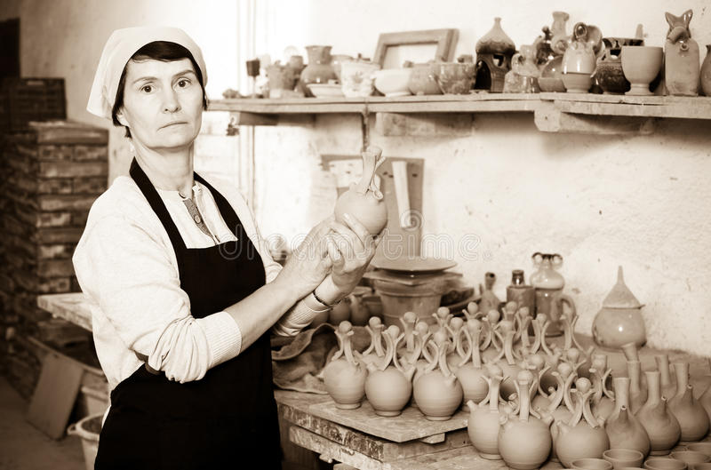Mature master among the pottery at the workshop. Cheerful elderly female master among the finished products in the pottery workshop stock images