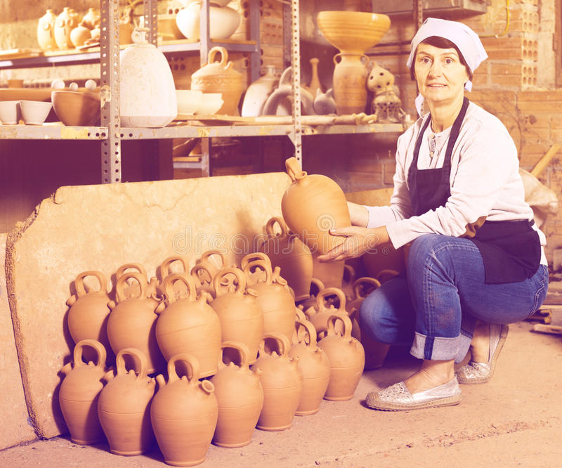 Mature master among the pottery at the workshop. Glad mature female master among the finished products in the pottery workshop royalty free stock image