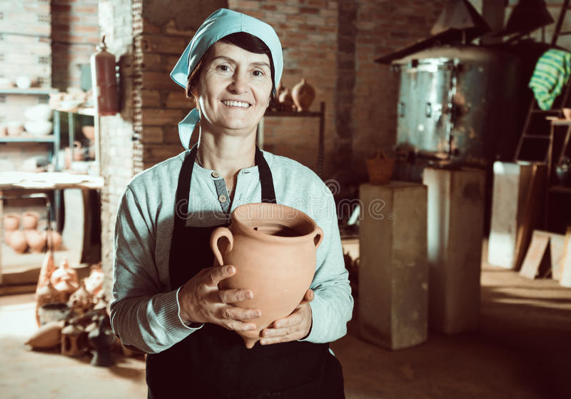 Mature master among the pottery at the workshop. Happy senior female master among the finished products in the pottery workshop stock photo