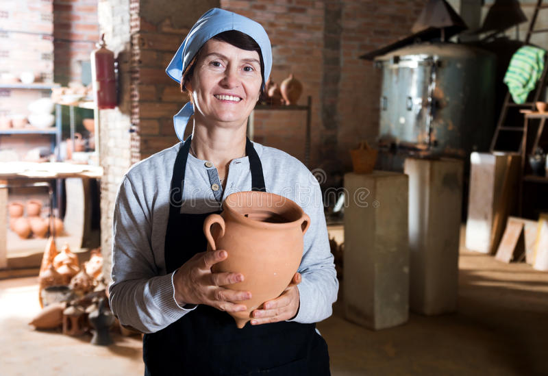 Mature master among the pottery at the workshop. Happy senior female master among the finished products in the pottery workshop royalty free stock photography