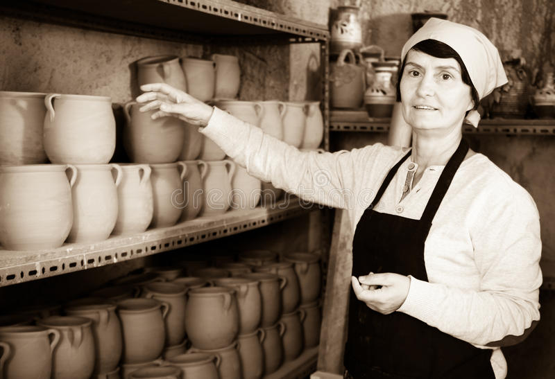 Mature master among the pottery at the workshop. Portrait senior female master among the finished products in the pottery workshop stock photo