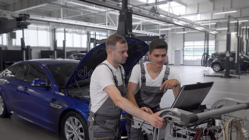 Mature mechanic and his assistant using computer at car repair station. Two car technicians repairing automobile, doing computer diagnostics. Car service stock images