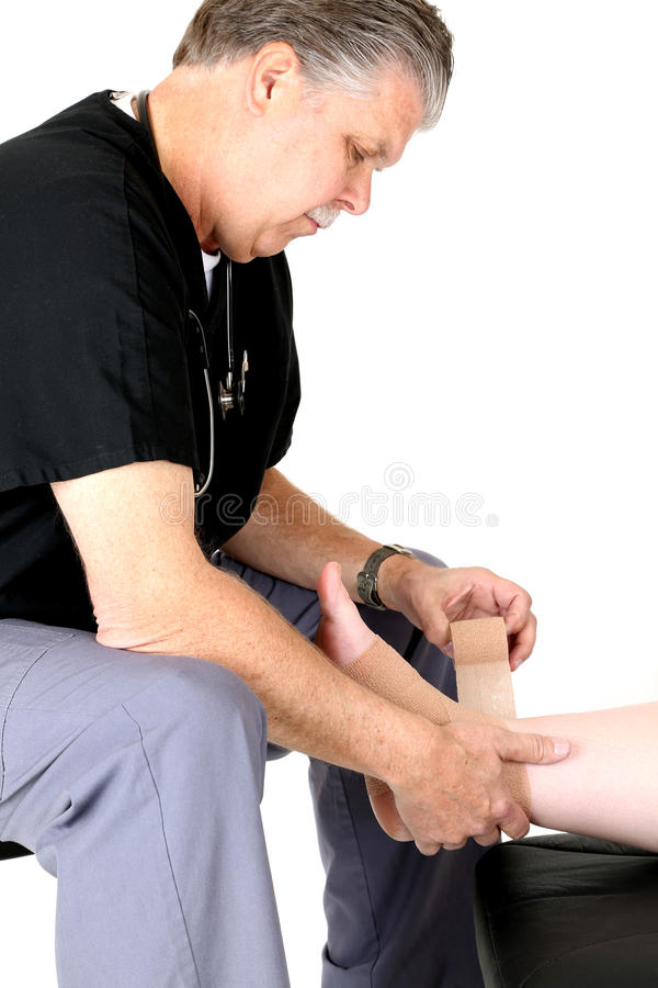 Mature medical doctor wrapping patients ankle royalty free stock photo