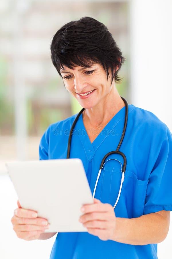 Mature medical worker tablet stock images