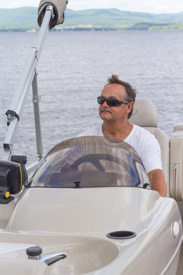 Free Mature Men Driving A Pontoon Boat On A Lake Stock Image - 56908801