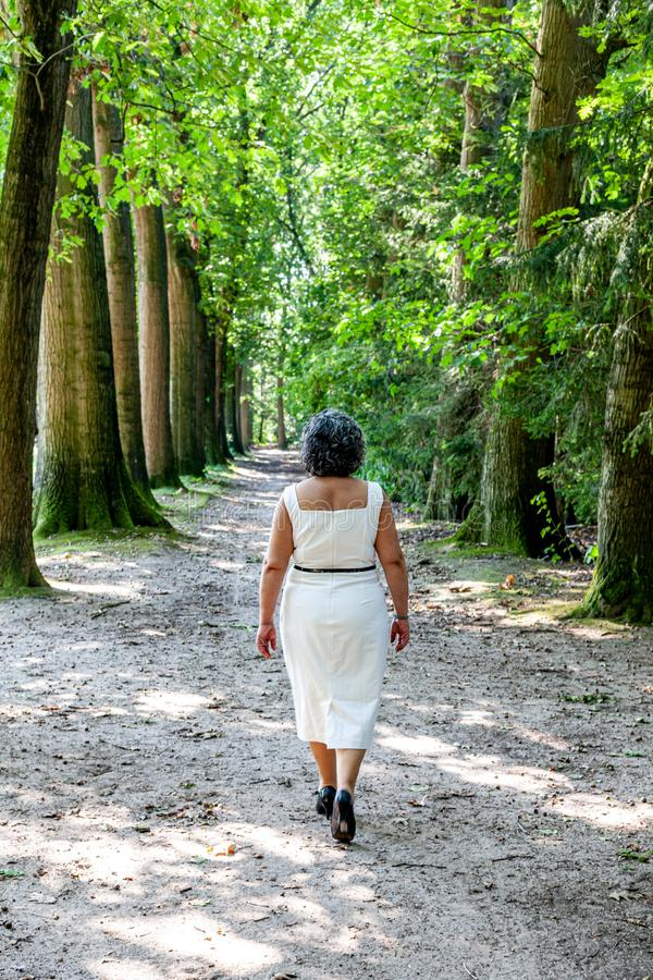 Mature Mexican woman in a white dress walking away from the camera on a dirt path between trees in the forest royalty free stock photos