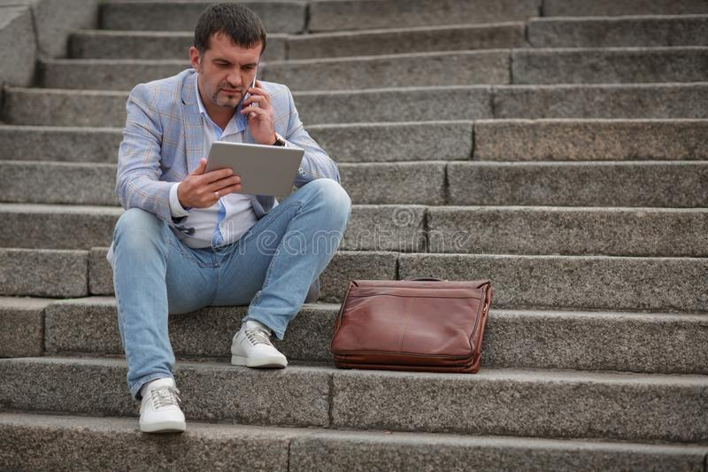 Business man with tablet on the stairs background. Worker talking on a phone. Business conversation concept. Copy space. stock image