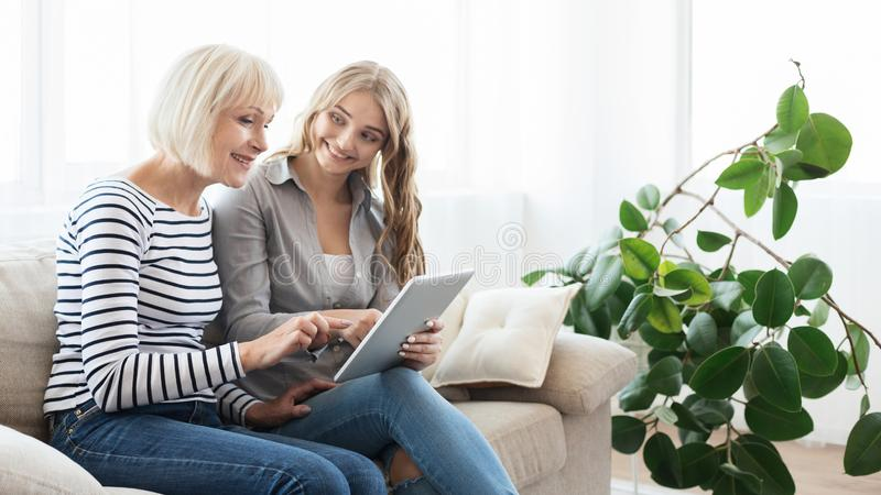 Mature mother and adult daughter with digital tablet stock photography