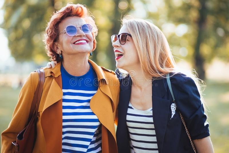 Mature mother and adult daughter enjoying a day in the park stock photo