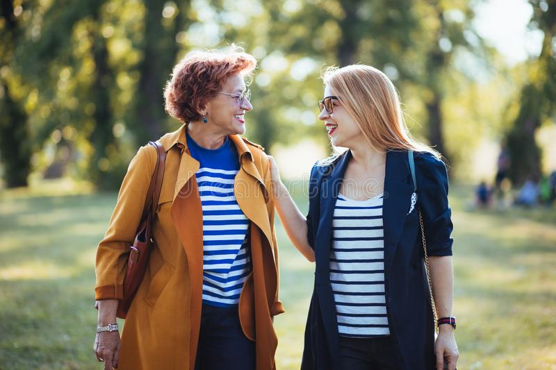Mature mother and adult daughter enjoying a day in the park royalty free stock photo