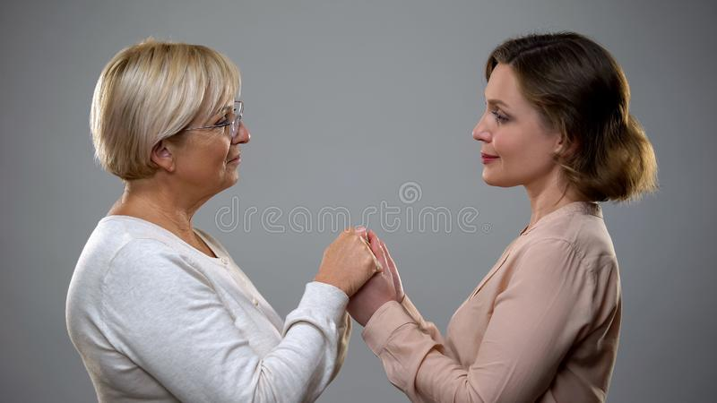 Mature mother and adult daughter holding hands looking each other, closeness royalty free stock photo