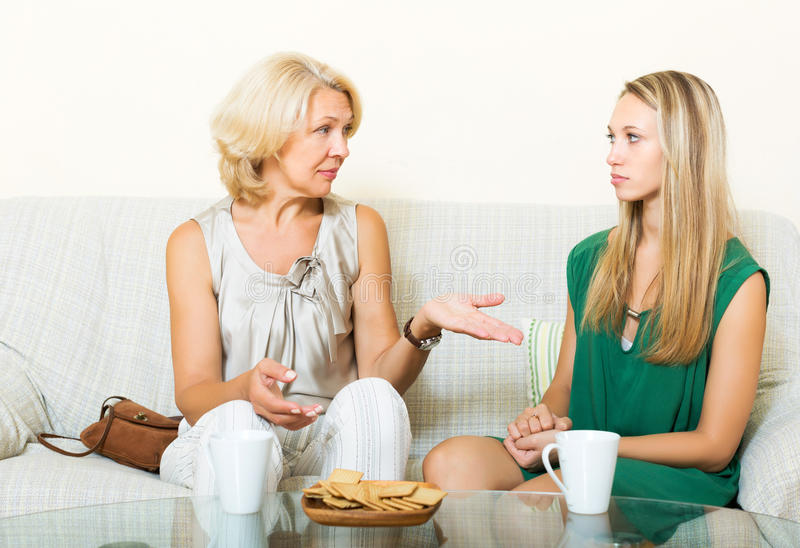 Mature mother and daughter talking. Serious mature mother and daughter talking in home royalty free stock image