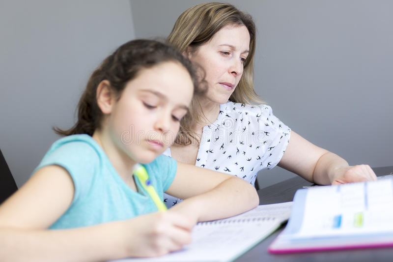 Mature mother helping her child with homework at home. royalty free stock image