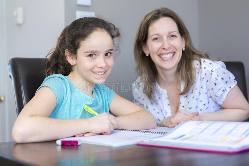 Mature mother helping her child with homework at home. royalty free stock photo