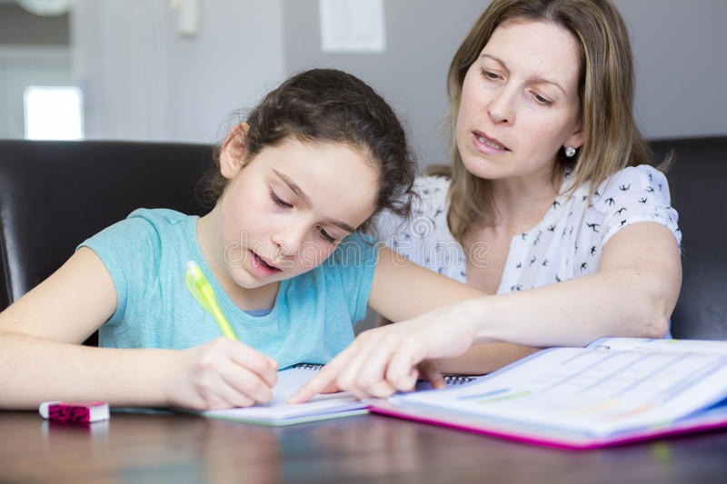 Mature mother helping her child with homework at home. royalty free stock photography