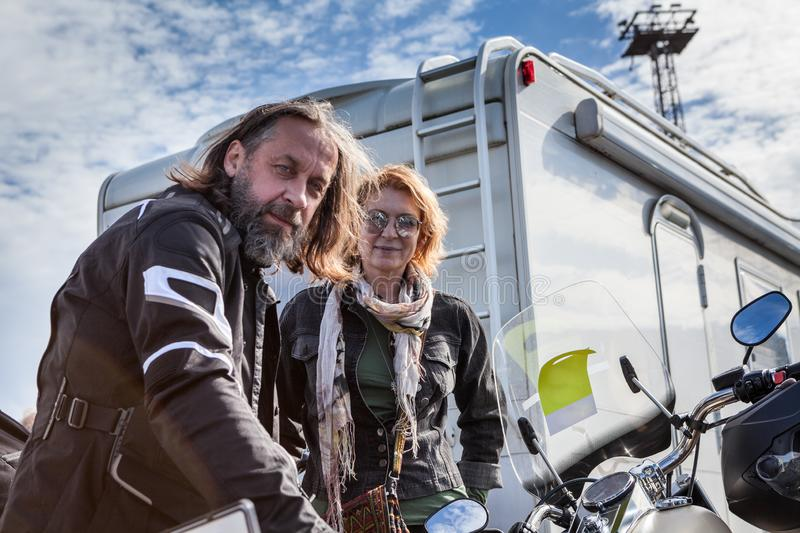 Mature motorcyclist couple travel with motorbike, sitting on motorcycle, waiting loading on ferry royalty free stock photos