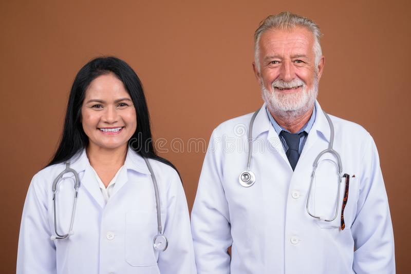 Mature multi-ethnic couple doctors against brown background stock photos