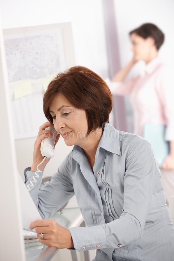 Mature office worker woman using landline phone stock photos
