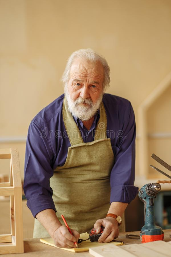 Mature old craftsman with white beard, moustache nad hair developing a design. Close up portrait of mature old craftsman with white beard, moustache nad hair stock photos