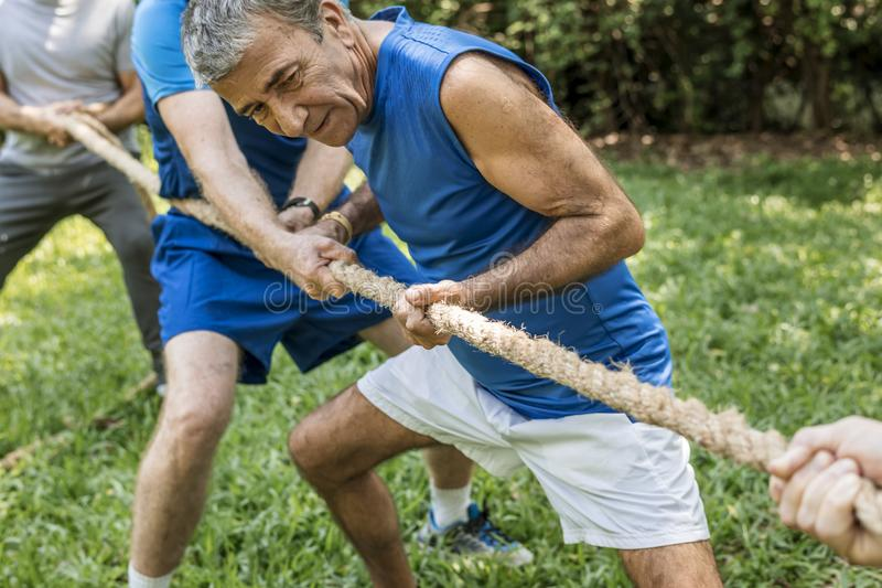 Mature people playing in tug of war royalty free stock photos