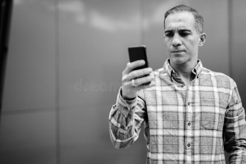 Mature Persian man against glossy wall in black and white stock images