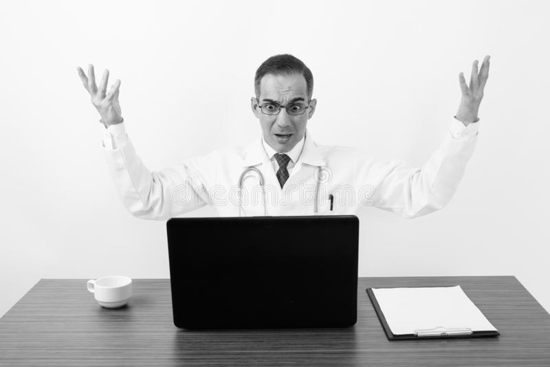 Mature Persian man doctor behind desk in black and white stock photo