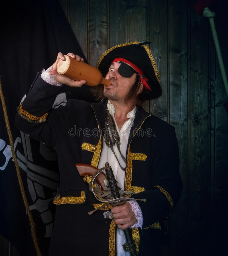 Mature Pirate Capitan. Adult pirate captain in a traditional costume and with weapons drinks rum from a clay bottle against the background of a jolly roger stock image