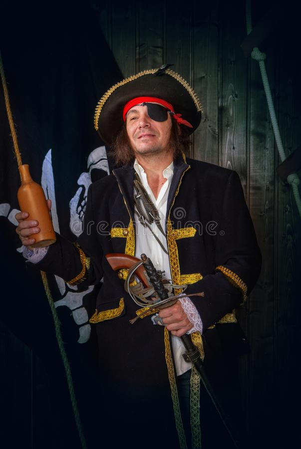 Mature Pirate Capitan. Adult pirate captain in a traditional costume and with weapons drinks rum from a clay bottle against the background of a jolly roger royalty free stock images