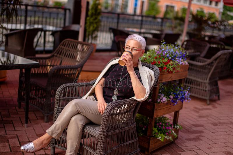 Mature pleasant woman drinking tea in her favourite coffee shop stock photography