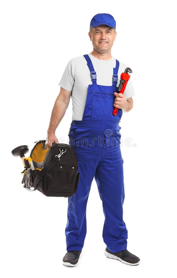 Mature plumber with pipe wrench and tool bag royalty free stock photography