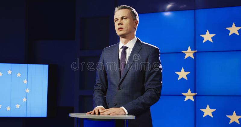 Confident businessman conducting conference in public. Mature politician in elegant suit standing on stage in light against screen with EU flag and giving speech royalty free stock images