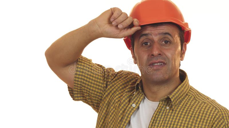 Mature professional builder in hardhat looking disappointed. Close up of a Hispanic mature male engineer wearing hardhat looking disappointed and upset shaking royalty free stock photos