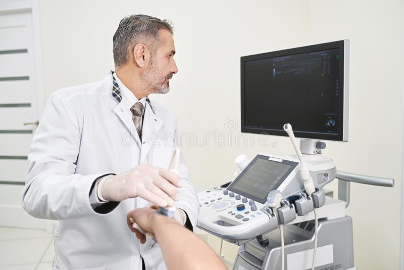 Doctor doing ultrasound examination of patinet`s wrist. Mature and professional doctor holding hand of patient, doing ultrasound examination. Therapist using stock images