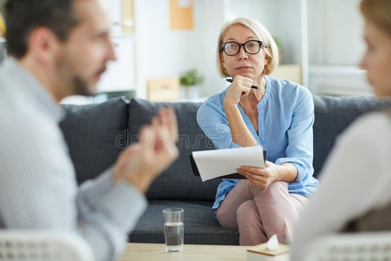 Mature professional. Counselor sitting on couch in front of arguing couple and listening to their talk stock photo