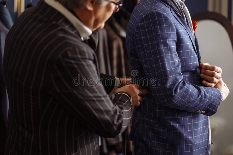Mature professional Tailor taking measure leg measuring of client customer stock photos