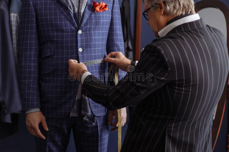 Mature professional Tailor taking measure leg measuring of client customer royalty free stock photo