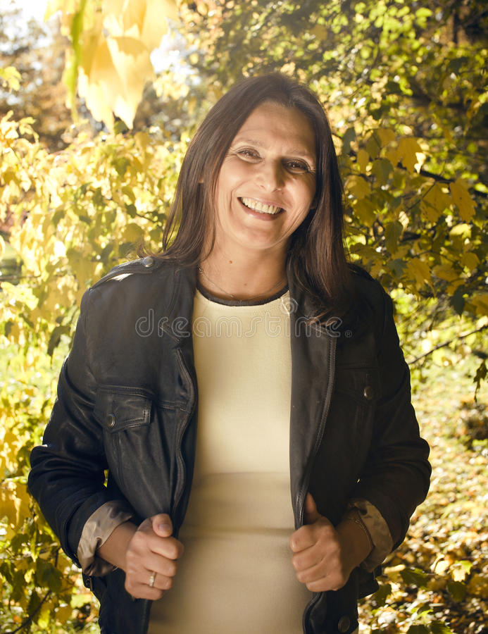 Mature real brunette woman in green spring park, lifestyle concept outside. Sunlight everywere stock photo