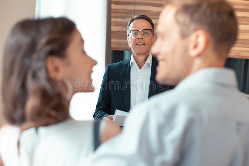 Mature realtor looking at couple while talking to them stock photos
