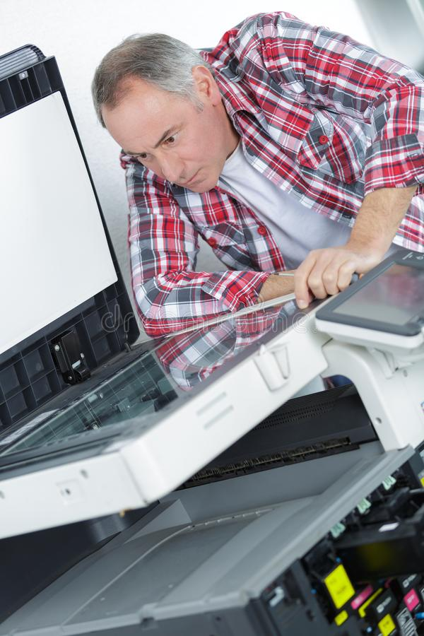 Mature repairman fixing printer machine royalty free stock image