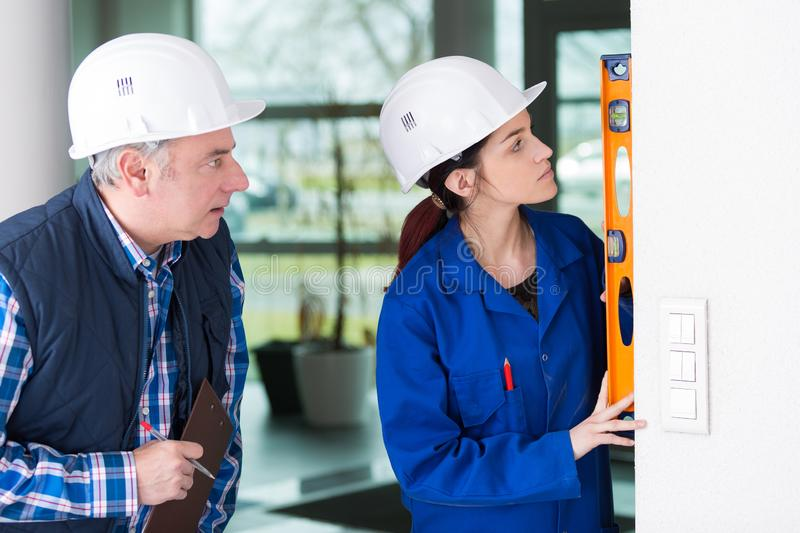Mature repairman helping woman to use builder level royalty free stock photography