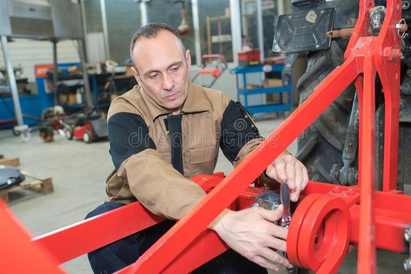 Mature repairman repairs tractor royalty free stock photos