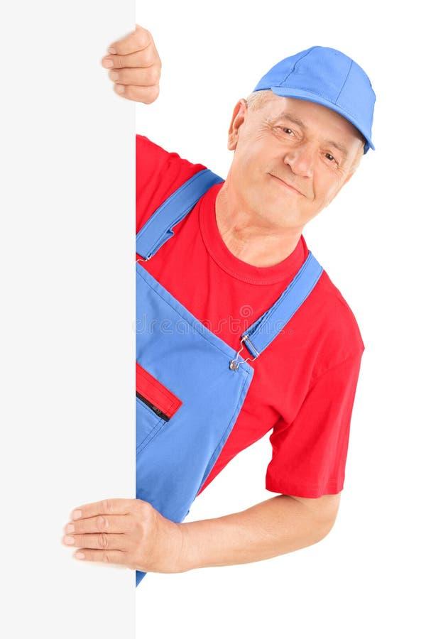 Mature repairman smiling and posing behind a blank panel stock photos