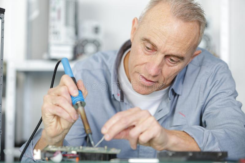 Mature repairman working in technical support fixing computer laptop tr royalty free stock image