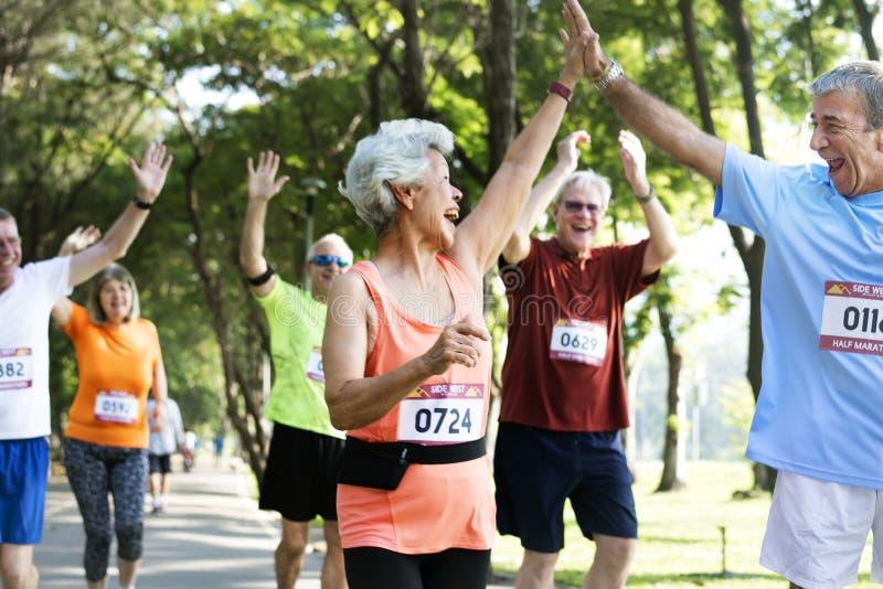 Mature runners running in a race stock photos