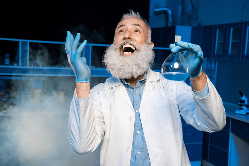 Mature scientist in lab coat holding flask with reagent at laboratory stock images