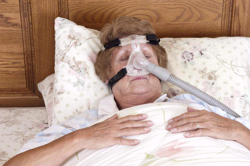 CPAP Sleep Apnea Machine, Senior Woman. Mature senior woman with CPAP sleep apnea machine lying on bed in bedroom. Used by people with sleeping disorders and stock images