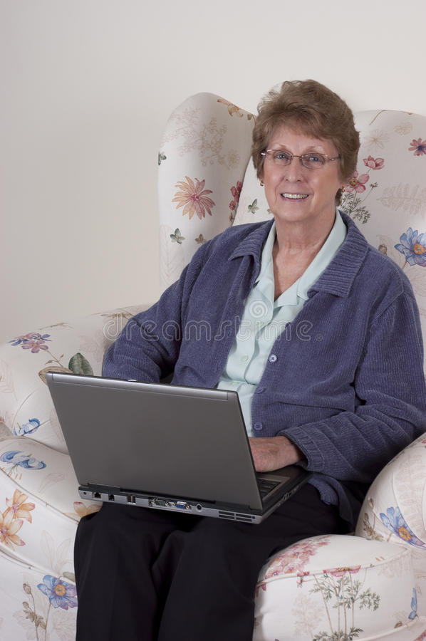 Mature Senior Woman Laptop Computer, Happy Smile. Mature senior woman using laptop computer with a happy smile. Grandma may be smiling with what she sees on the royalty free stock photography