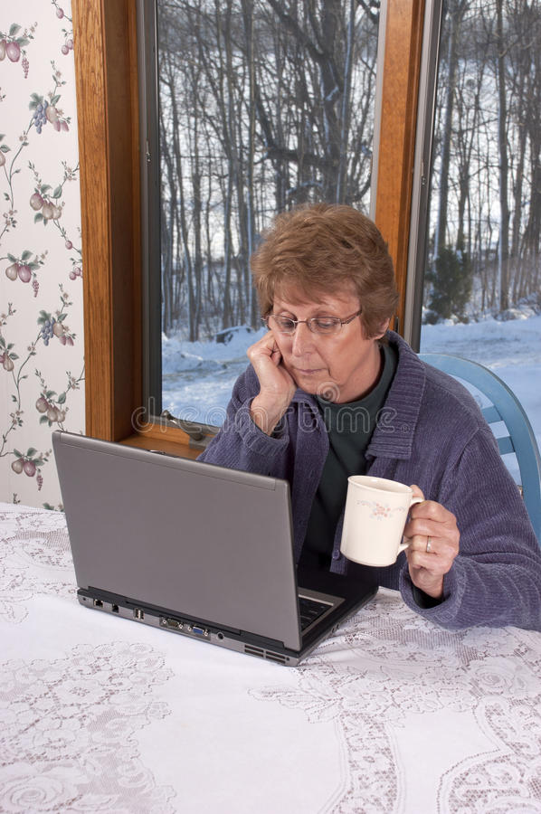 Mature Senior Woman Laptop Computer House Home. Mature senior woman using laptop computer while relaxing and drinking coffee or tea while at home. Grandma here stock image